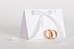 Gli anelli di cerimonia nuziale ed invitano con l'arco bianco Fotografie Stock Libere da Diritti