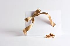 Gli anelli di cerimonia nuziale ed invitano con l'arco dorato Immagini Stock Libere da Diritti
