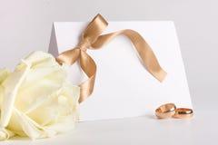 Gli anelli di cerimonia nuziale ed invitano con sono aumentato Immagini Stock