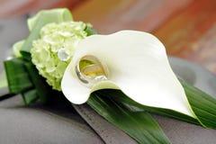 Gli anelli di cerimonia nuziale su un calla bianco lilly fiorisce Immagini Stock Libere da Diritti