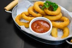 Gli anelli di cipolla deliziosi con salsa al pomodoro serviscono sulla ciotola del metallo immagini stock libere da diritti