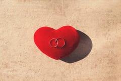 Gli anelli di oro di nozze due su un cuore rosso del cuscino modellano sopra il fondo della carta del mestiere Immagine Stock