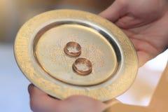 Gli anelli dorati su un piatto di oro fotografia stock