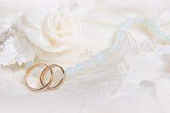 Gli anelli ed il bianco di cerimonia nuziale sono aumentato Immagini Stock