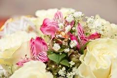 Gli anelli sui fiori, in una scatola, su un tessuto bianco sui giocattoli, colori, dettagli di nozze, fedi nuziali Immagini Stock Libere da Diritti