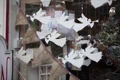 Gli angeli di carta suonano la tromba nei tubi Figure di carta come decorazione della finestra del negozio nel Natale Immagine Stock