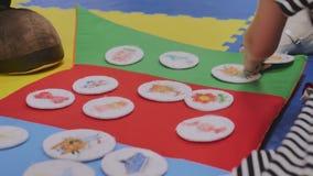 Gli animatori giocano con i bambini nella stanza dei bambini negli autoadesivi della peluche del giocattolo con le immagini, solt video d archivio