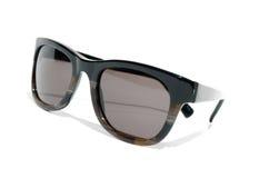 Gli anni 80 freddi designano gli occhiali da sole contro una priorità bassa bianca Fotografia Stock