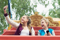 Gli anni dell'adolescenza felici guidano sul carosello e fanno il selfie Immagine Stock