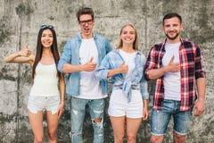 Gli anni dell'adolescenza positivi stanno stando sul fondo grigio e stanno mostrando il simbolo dei simili Sono felici e soddisfa Fotografia Stock Libera da Diritti