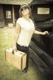 Gli anni 20 felici hanno vestito la valigia della tenuta della ragazza accanto all'automobile d'annata Fotografia Stock Libera da Diritti