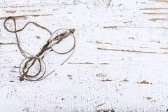 Gli anni 20 rotondi antichi degli occhiali su superficie di legno dipinta, sul posto per testo o sugli elementi di progettazione Fotografia Stock