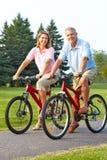 Gli anziani coppia biking Immagini Stock
