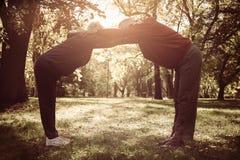 Gli anziani coppia l'esercitazione e l'allungamento delle armi insieme dentro Fotografie Stock Libere da Diritti