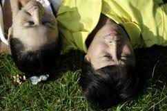 Gli anziani coppia la menzogne sull'erba Fotografie Stock