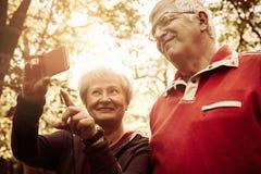 Gli anziani si accoppiano in abbigliamento di sport che prende l'immagine di auto nella p fotografie stock libere da diritti