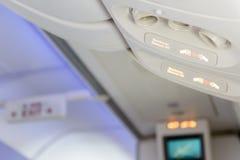 Gli apparecchi elettronici fuori e fissano il segno della cintura di sicurezza dentro l'aeroplano Immagini Stock Libere da Diritti