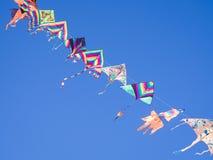 Gli aquiloni colorati volano in una fila nel cielo blu che appende su un filo Immagini Stock