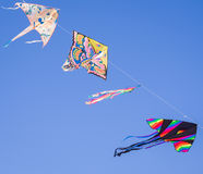 Gli aquiloni colorati volano in una fila nel cielo blu che appende su un filo Fotografia Stock
