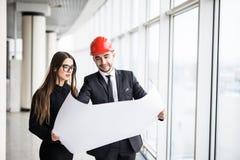 Gli architetti dell'uomo d'affari esaminano l'architetto di carta della donna di affari di piano in ufficio per discutere i proge Fotografie Stock Libere da Diritti