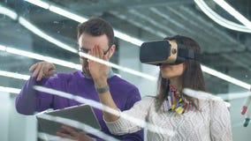 Gli architetti utilizzano i vetri e la compressa di VR per lavorare con un modello su un bordo stock footage