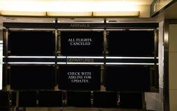 Gli arrivi dell'aeroporto ed i segni di partenza che indicano che tutti i voli sono annullati e che viaggiatori dovrebbero contro fotografia stock