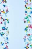 Gli articoli per ufficio sotto forma di bottoni e di graffette colorati sul a destra e a sinistra orlano della foto verticale fotografia stock libera da diritti