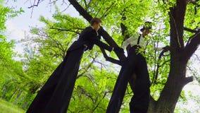 Gli artisti della via e del mimo che imbrogliano sui trampoli giocano nel parco archivi video