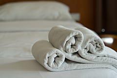 Gli asciugamani bianchi rotolano sul letto nella camera da letto dell'hotel fotografia stock libera da diritti