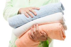 Gli asciugamani della stazione termale della tenuta della mano della donna impilano il bianco isolati Fotografie Stock Libere da Diritti