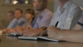 Gli ascoltatori del primo piano si siedono e tengono le penne ed i taccuini alla tavola video d archivio