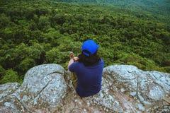 Gli asiatici dell'uomo viaggiano si rilassano nella festa Natura della montagna di vista sulle scogliere immagine stock libera da diritti
