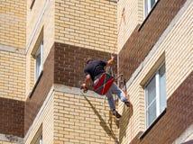 Gli assemblatori perforano una parete a casa facendo uso di attrezzatura rampicante immagine stock