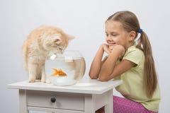 Gli assomigliare della ragazza ad un gatto vuole prendere il pesce rosso Fotografia Stock