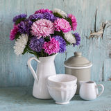 Gli aster dei fiori in un bianco hanno smaltato il lanciatore e le terrecotte dell'annata - ciotola ceramica e barattolo smaltato fotografia stock libera da diritti