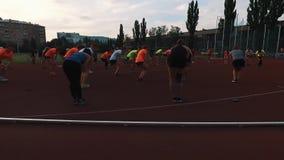 Gli atleti allegri raggruppano l'allungamento delle ginocchia allo stadio nell'area del dormitorio video d archivio