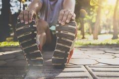 Gli atleti asiatici stanno allungando le sue gambe prima che correndo risolva sulla strada in parco fotografia stock