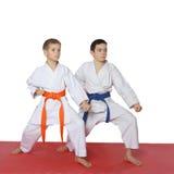 Gli atleti con una cinghia blu e la cinghia arancio stanno in scaffale Fotografia Stock