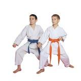 Gli atleti su un fondo bianco con una cinghia blu e la cinghia arancio stanno in scaffale Fotografia Stock