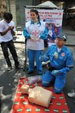 Gli attivisti della croce rossa insegnano al pronto soccorso della gente su una via della città Fotografie Stock