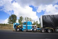 Gli autisti di camion che riparano il grande camion dei semi dell'impianto di perforazione con il cappuccio aperto radrizzano fotografia stock libera da diritti