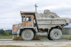 gli autocarri con cassone ribaltabile Gran-gialli della cava producono il trasporto dei minerali immagine stock