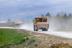 gli autocarri con cassone ribaltabile Gran-gialli della cava producono il trasporto dei minerali immagini stock