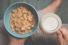 Gli azzurri della tenuta della donna hanno colorato la ciotola di fiocchi di mais saporiti del cereale immagini stock