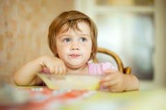gli Due-anni di bambino mangia dal piatto Fotografie Stock