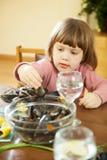 gli Due-anni di ragazza mangia le cozze Fotografia Stock