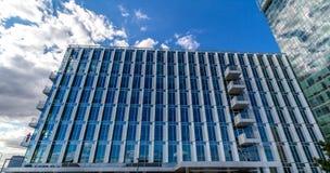 Gli edifici per uffici riflettenti di vetro contro cielo blu con le nuvole ed il sole si accendono Immagine Stock Libera da Diritti