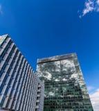 Gli edifici per uffici riflettenti di vetro contro cielo blu con le nuvole ed il sole si accendono Fotografie Stock