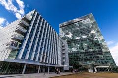 Gli edifici per uffici riflettenti di vetro contro cielo blu con le nuvole ed il sole si accendono Immagini Stock Libere da Diritti