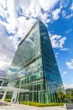 Gli edifici per uffici riflettenti di vetro contro cielo blu con le nuvole ed il sole si accendono Immagini Stock